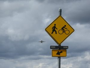 Pedestrian and bike crossing sign at Marine Drive with airplane sm